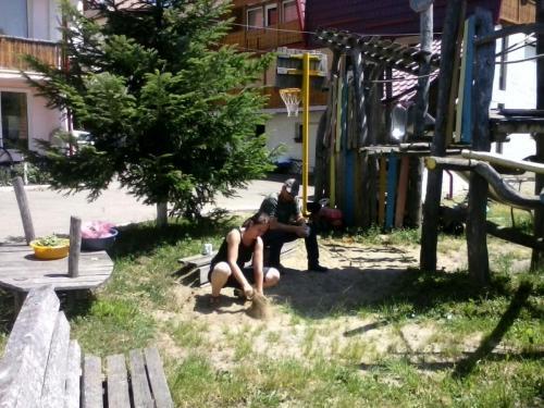 Sara und Fredi rupfen das Gras aus dem Sandkasten